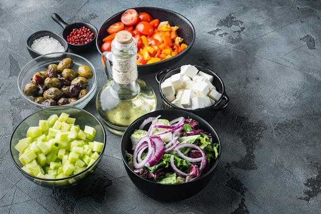 Ingredienti principali dell'insalata greca: mix di olive fresche, formaggio feta, pomodori, pepe, su sfondo grigio con copia spazio per il testo