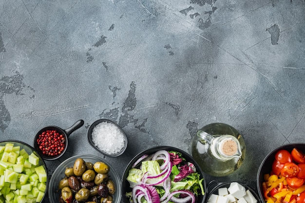 Ingredienti principali insalata greca mix di olive fresche, formaggio feta, pomodori, pepe, sul tavolo grigio, vista dall'alto laici piatta