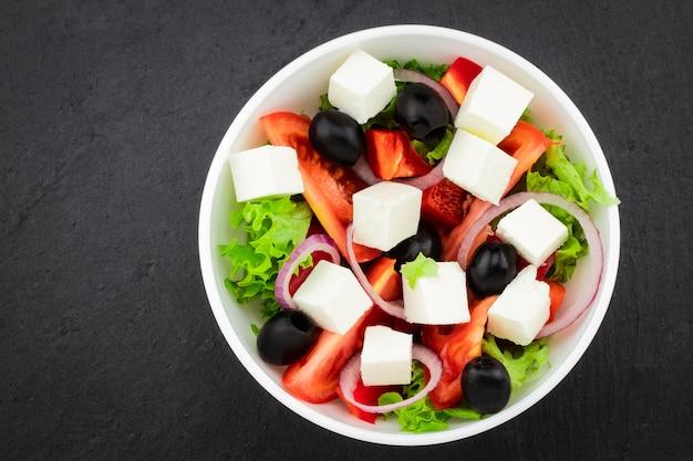 Insalata greca con verdure fresche, formaggio feta e olive nere su sfondo scuro.