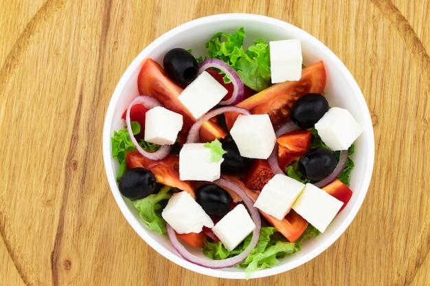 Insalata greca con verdure fresche, formaggio feta e olive nere su fondo di legno. vista dall'alto.