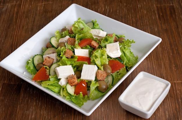 Insalata greca con verdure fresche, formaggio feta, olive verdi e fette biscottate.