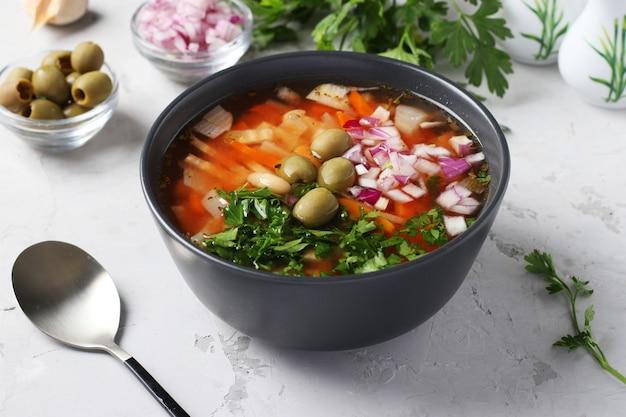 Zuppa di pomodoro greca con verdure, olive verdi e fagioli bianchi in una ciotola scura su sfondo grigio. avvicinamento Foto Premium