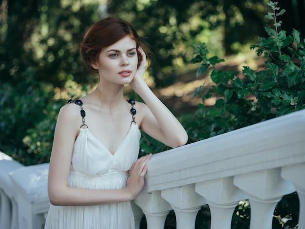 Donna greca in abito bianco nel parco natura moda estate