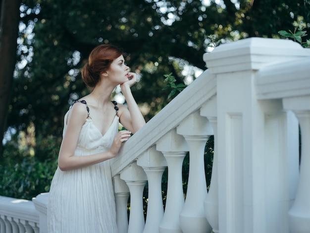 Donna greca in abito bianco nella natura romantica del parco