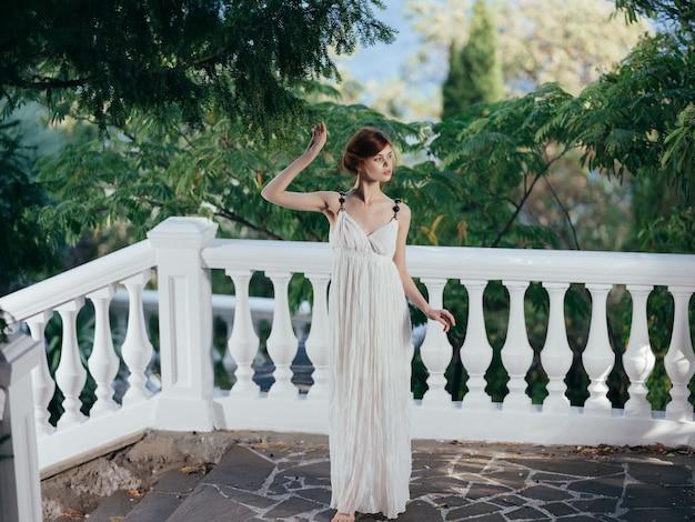 Donna greca in abito bianco in posa nel parco