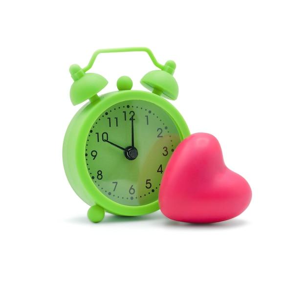 Sveglia verde con cuore rosa su bianco con spazio copia tempo per l'amore e un concetto sano