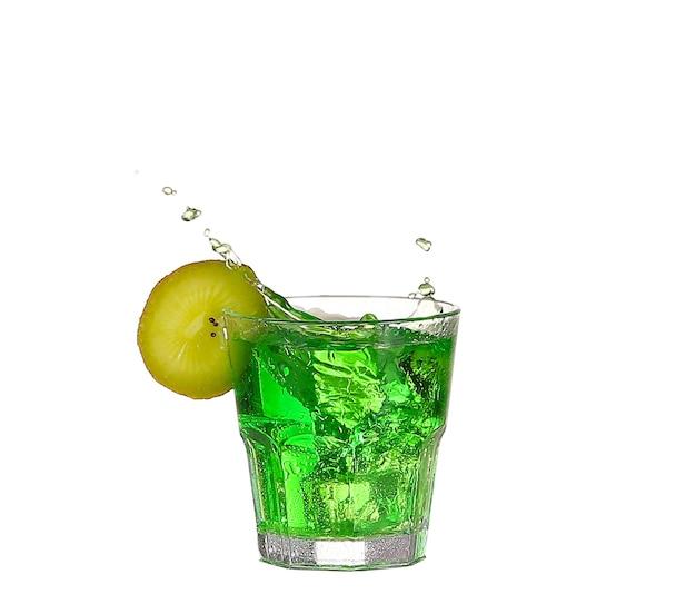 Cocktail verde dell'alcool con spruzzata e calce verde isolata su bianco