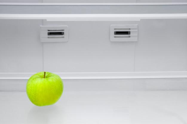 Mela verde in un frigorifero vuoto.