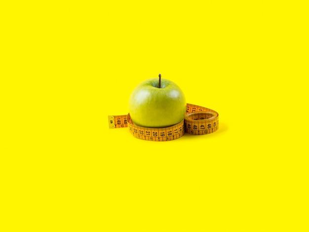 Mela verde con nastro adesivo di misurazione su giallo