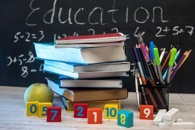 Mela verde con pila di libri e forniture per scrivere contro la lavagna. concetto di educazione