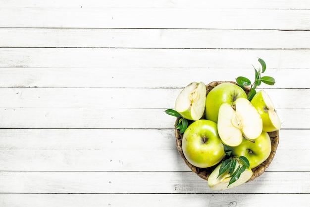 Mele verdi in un cestino. su un tavolo di legno bianco.