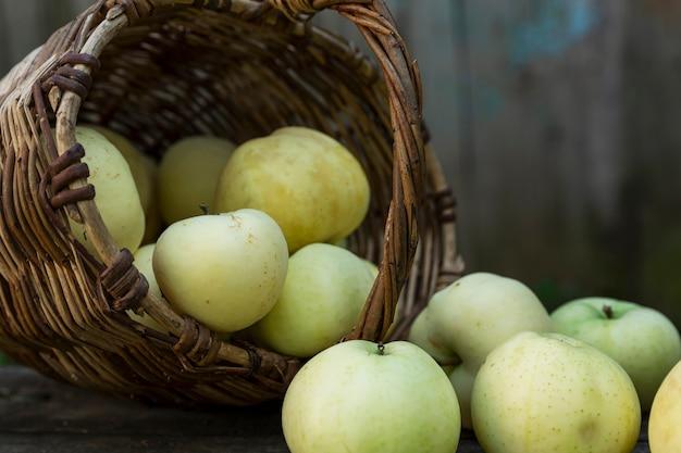 Mele verdi sparse da un cesto di vimini su un tavolo di legno. fresco raccolto autunnale. salute e vitamine dalla natura. avvicinamento.