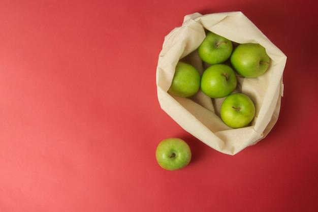Mele verdi nella borsa di totalizzatore bianca, fondo rosso. concetto di scarto zero.