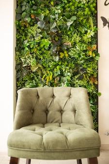 Poltrona verde sullo sfondo di un muro d'erba