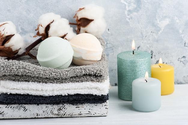 Bombe da bagno aromatiche verdi nella composizione spa con fiori secchi e asciugamani