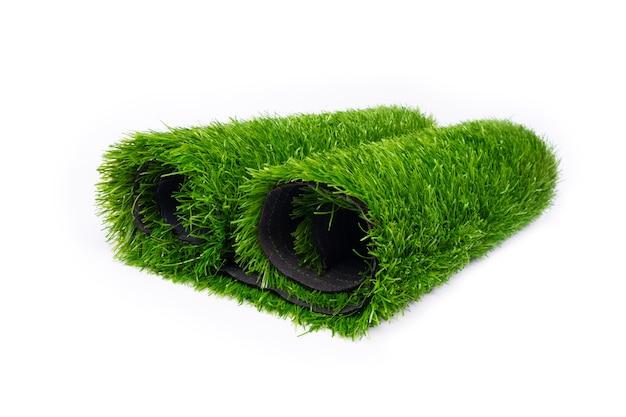 Tappetino verde erba artificiale, rotolo di prato su sfondo bianco.