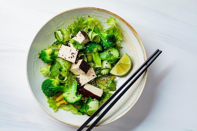 Insalata asiatica verde con broccoli e tofu affumicato in una ciotola bianca, sfondo bianco.