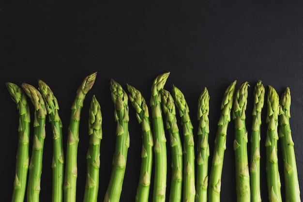 Asparagi verdi sulla superficie scura pronti per la cottura
