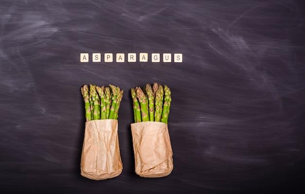 Asparagi verdi in un sacchetto di carta su una lavagna nera. raccolto stagionale primaverile. lay piatto, copia spazio. concetto di cibo sano. vista dall'alto.