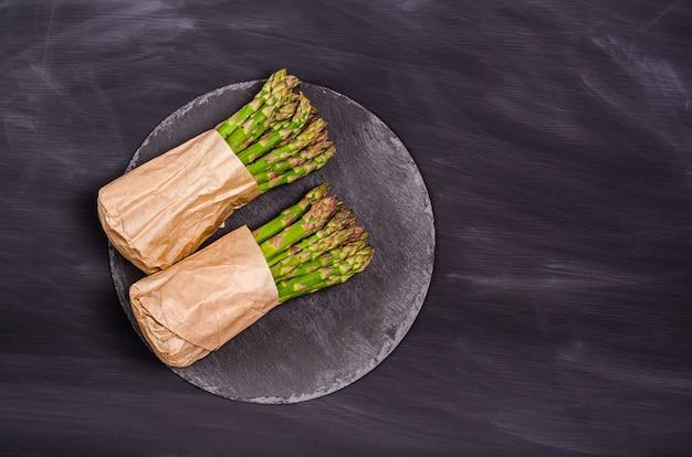 Asparagi verdi in un sacchetto di carta su una tavola di ardesia su sfondo nero. raccolto stagionale primaverile. lay piatto, copia spazio. concetto di cibo sano. vista dall'alto.