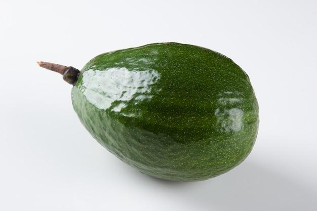 Frutto di avocado verde isolato su superficie bianca.