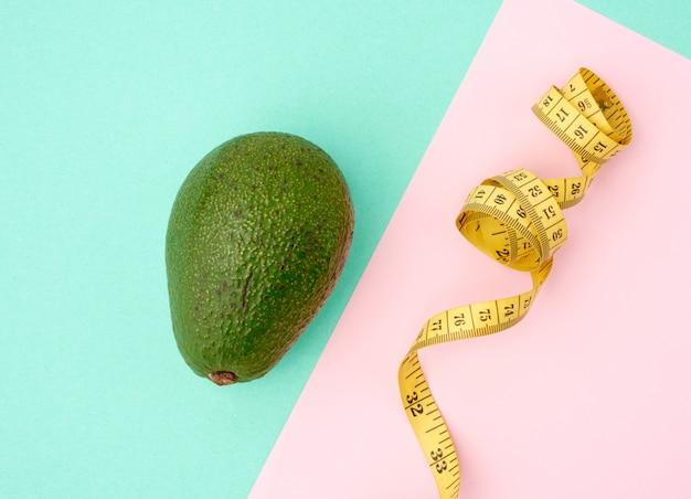 Di avocado verde e un nastro giallo di misurazione contorto su uno spazio rosa verde