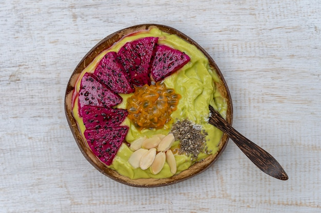 Frullato di avocado verde in una ciotola di cocco con frutto del drago, frutto della passione, scaglie di mandorle, scaglie di cocco e semi di chia per colazione, primo piano. il concetto di alimentazione sana, superfood. bali, indonesia