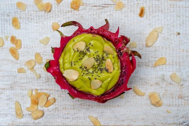 Frullato di avocado verde nella pelle del frutto del drago con scaglie di mandorle e semi di chia per colazione, primo piano. il concetto di alimentazione sana, superfood. bali, indonesia
