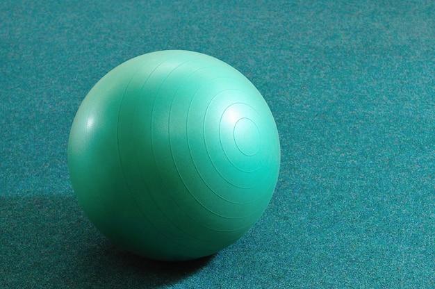 Palla verde per il fitness su sfondo azzurro