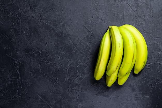 Banane verdi. sfondo nero. vista dall'alto. spazio per il testo