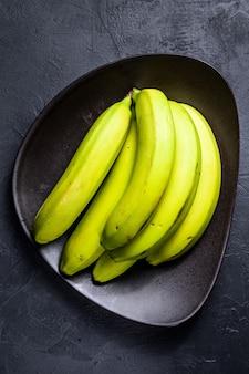 Banane verdi su un piatto. sfondo nero. vista dall'alto. frutta tropicale