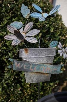 Cestino verde con fiori freschi e testo del segno di benvenuto scritto in nero sul muro vicino alla porta