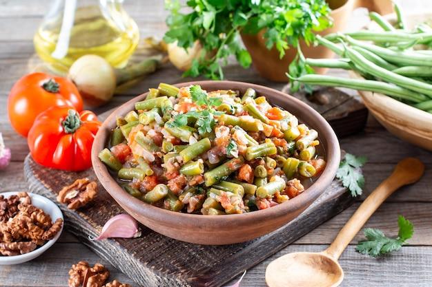 Fagiolini con verdure e pomodori. fondo di cottura del cibo, tavolo rustico in legno d'epoca.
