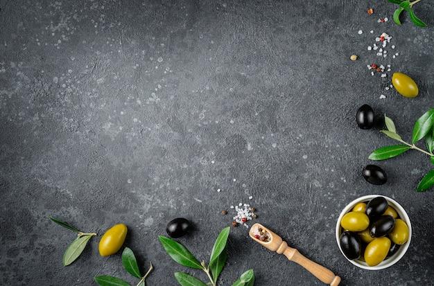 Olive verdi e nere con foglie su superficie scura. copia spazio, direttamente sopra.