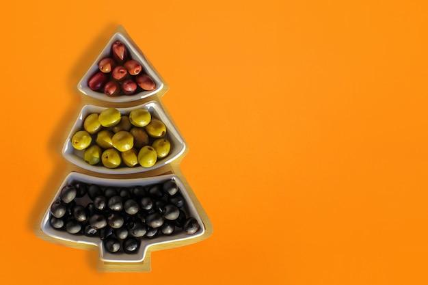 Olive verdi, nere e rosse in un vaso a forma di albero di natale su fondo rosso.