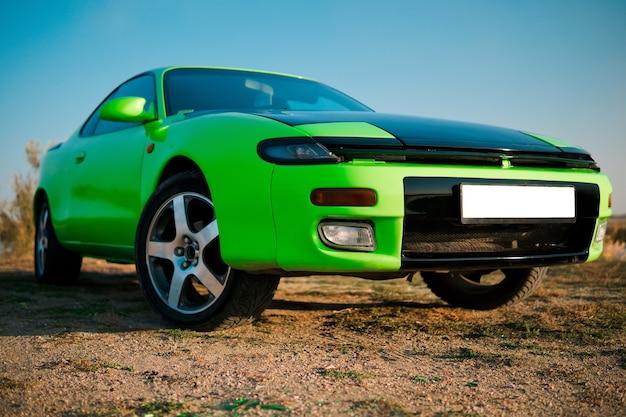 Auto coupé sportiva verde e nera con grandi ruote. oldtimer giapponese.