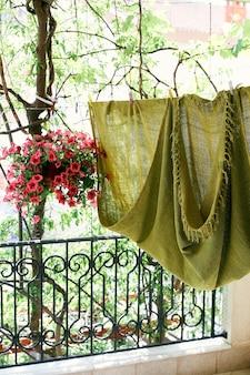 Una coperta verde e un vaso di fiori rossi sono appesi sul balcone