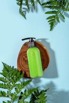 Bottiglia verde di siero viso idratante su podio in legno e sfondo azzurro. sfondo di benessere termale. trattamento di bellezza
