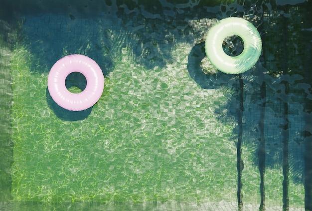 Piscina con fondo verde vista dall'alto con galleggianti rosa e verdi e ombre di palme. rendering 3d