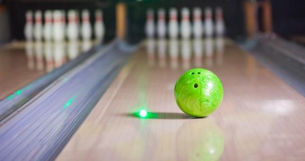 Palla da bowling verde messa sul vicolo con perno di bowling offuscata