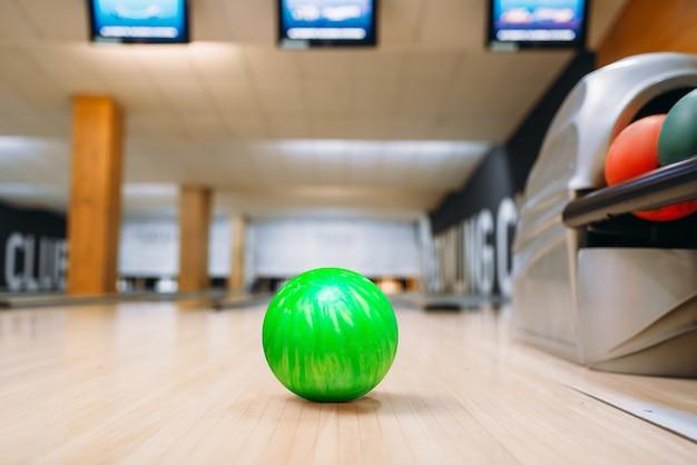 Palla da bowling verde sul pavimento di legno nel club, vista del primo piano, nessuno. concetto di gioco della ciotola
