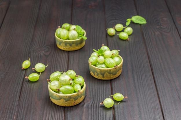 Ciotole verdi con uva spina verde. fondo in legno scuro. vista dall'alto