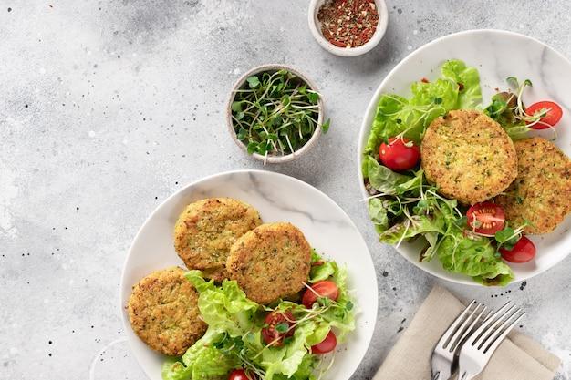 Hamburger di broccoli verdi e quinoa in piatti con insalata dieta a base vegetale