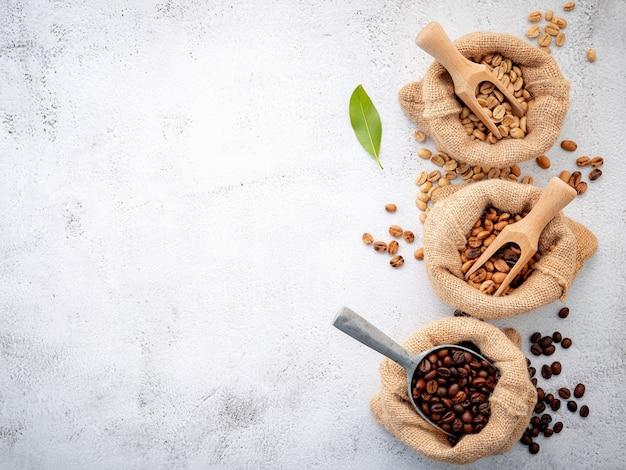Chicchi di caffè tostati decaffeinati verdi e marroni non torrefatti e scuri in sacchi di canapa con palette montate su cemento bianco.