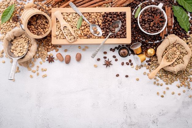 Chicchi di caffè tostati non torrefatti e scuri decaffeinati verdi e marroni in una scatola di legno con le palette installate su cemento bianco.