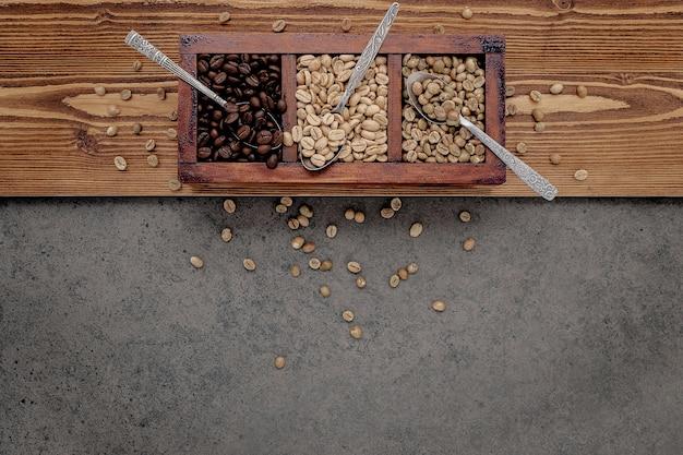 Chicchi di caffè tostati non torrefatti e scuri verdi e marroni in una scatola di legno con cucchiai installati su cemento scuro.
