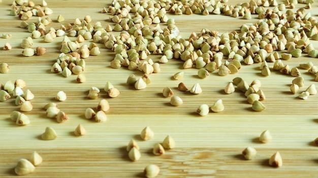 Semi di grano saraceno verde su uno sfondo di legno. ottimo cibo. semole salutari. cibo vegetariano crudo biologico non fritto. il concetto di una dieta sana, equilibrata e dietetica. copia spazio.