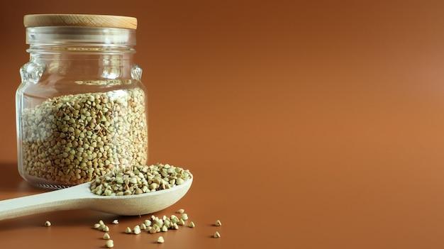 Germogli di grano saraceno verde in un barattolo di vetro con un cucchiaio di legno. concetto di cibo vegano crudo. cibo organico. il concetto di dieta, perdita di peso, alimentazione sana e corretta. copia spazio. spazio per il testo.