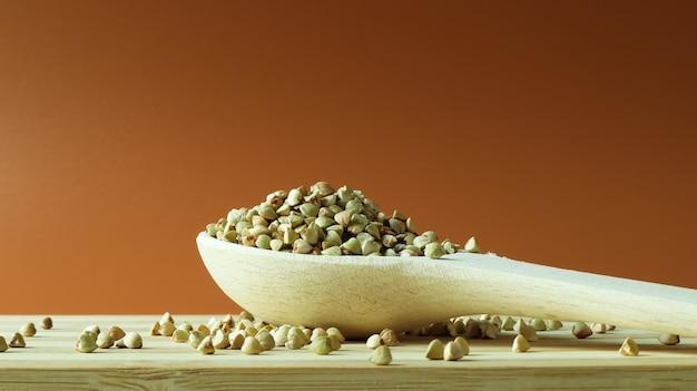 Grano saraceno verde in un cucchiaio di legno su uno spazio marrone. ottimo cibo. semole sane.
