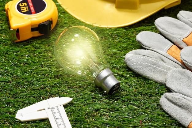 Concetto di bioedilizia e risparmio energetico: progetto di casa e strumenti di lavoro sull'erba